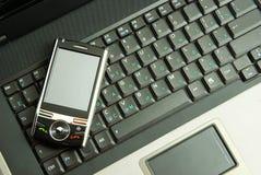 Mobiele telefoon op laptop Stock Afbeeldingen