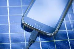 Mobiele telefoon op zonnelader Stock Afbeeldingen