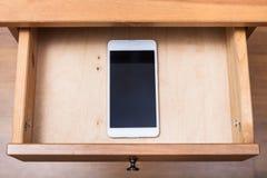 Mobiele telefoon in open lade royalty-vrije stock afbeeldingen