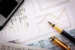 Mobiele telefoon, pen en documenten met grafieken Stock Afbeelding