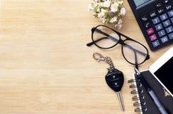 Mobiele telefoon, sleutel, glazen en calculator op houten textuur backgr Stock Afbeeldingen