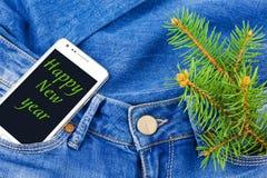 Mobiele telefoon in zak van jeans stock foto's