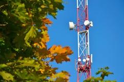 Mobiele telefoonmededeling de radiotv-toren, mast, antennes van de celmicrogolf en zender tegen de blauwe hemel en de bomen Stock Foto