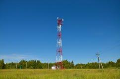 Mobiele telefoonmededeling de radiotv-toren, mast, antennes van de celmicrogolf en zender tegen de blauwe hemel en de bomen Stock Fotografie
