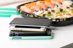 Mobiele telefoons en sushi stock foto