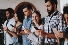 Mobiele telefoons Jonge mensen Tribune in lijn bezig royalty-vrije stock foto