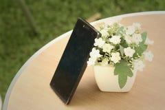 Mobiele Telefoons met bloemen op de lijst stock foto's