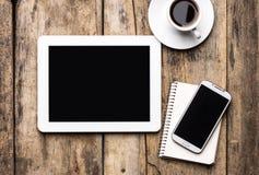 Mobil arbetsplats med den minnestavlaPC, telefonen och koppen kaffe Arkivbild