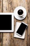 Mobil arbetsplats med den minnestavlaPC, telefonen och koppen kaffe Arkivbilder