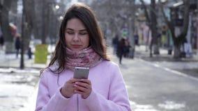 Mobil böjelse, den trevliga flickabrukssmartphonen som meddelar i samkväm, knyter kontakt på öppen luft stock video