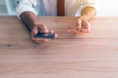 Mobil bankrörelsesmartphone app som används av affärsmannen Arkivbild