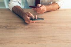 Mobil bankrörelsesmartphone app som används av affärsmannen Arkivfoto