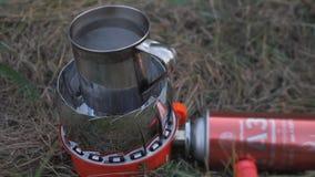 Mobil gasbrännareugn för gas Gascylinder förbindelse till gasmusikbandet metall rånar fyllt med vatten värmas på ett bärbart lager videofilmer