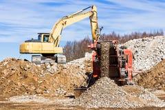 Mobil kross för crawlsimmare och grävskopaCrushing betong royaltyfri fotografi