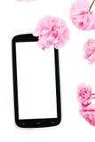 Mobil mądrze telefon otaczający różowymi czereśniowymi kwiatami Zdjęcia Royalty Free