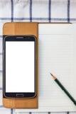 Mobil och dagbok på en vit bakgrund Arkivfoto