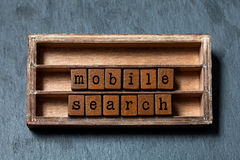 Mobil sökandebegreppstext Trähylla med texturerade kvarter och bokstäver Grå stenbakgrund, makro, mjuk fokus Upp fotografering för bildbyråer