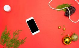 Mobil skärm för smart telefon på den röda skärmen för modell i jultid julgarneringar, kottar och granfilialer i bakgrund Arkivbilder