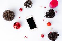Mobil skärm för smart telefon på tabellen med den isolerade vita skärmen för modell i jultid kottar och garneringar i bakgrund royaltyfri bild