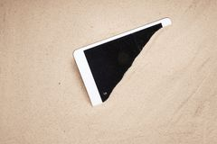 Mobil skärmskärm för minnestavla som täckas i sand på den skadade och borttappade försäkringreklamationen för strand arkivbild