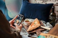 Mobil skjuta pizza för kvinna royaltyfri bild