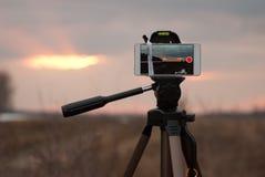 Mobil skytte, mobil på en tripod som tar bilder av aftonlandskapet, arkivbilder