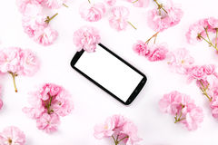 Mobil smart phone surrounded by pink cherry flowers Royalty Free Stock Photo