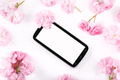 Mobil smart phone surrounded by pink cherry flowers Stock Photography