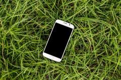 Mobil smartphone på gräset Arkivfoton