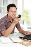 mobil telefon för bärbar datorman som texting genom att använda Arkivfoton
