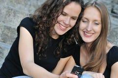 mobil telefon för vänner som ler två arkivfoto