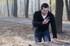Mobil telefona ed equipaggia con il sorriso Fotografia Stock