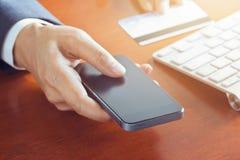 Mobila betalningar, affärsman som använder smartphonen och kreditkorten för online-shopping Royaltyfria Bilder