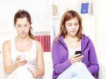 mobila telefoner tonårs- två för girs Arkivbild