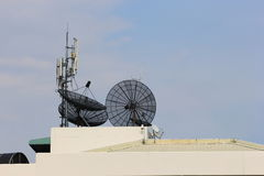 Mobile antenna and satellite dishes at building roof top Stock Photos
