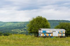 Mobile apiary trailer in meadow. View of Adygea republic nature, Russia. Mobile colorful apiary trailer in meadow. View of Adygea republic nature, Russia stock images
