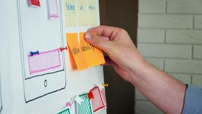 Mobile app developer planning new application layout on whiteboard stock footage
