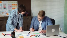 Mobile app developer sketching design of a new app and his coworker looking at his work. Stock Footage stock footage
