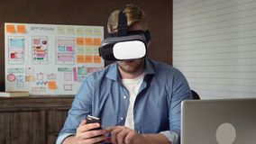 Mobile app developer testing his futuristic app concept using VR headset stock video