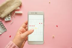 Mobile application to track your menstrual cycle and for marks. PMS and the critical days concept. Pain pills and personal care products, pink background stock photography
