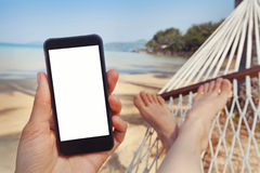 Mobile application for travels, phone in hand, beach Royalty Free Stock Photography
