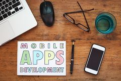 Mobile apps development. Paper and smartphone on the table royalty free stock image