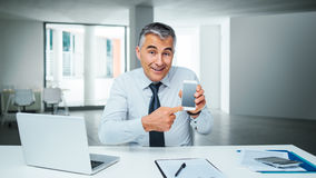 Mobile banking app. Smiling business man pointing at his smart phone and showing a mobile banking app Stock Image
