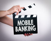 Mobile banking concept. Female hands holding movie clapper Stock Photo