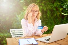 Mobile banking. High angle shot of attractive middle aged woman holding credit card and using laptop while e-banking from home royalty free stock photo