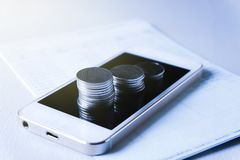 Mobile banking. Mobile application banking,coins on smartphones and book bank,soft focus,blur stock images