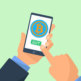 Mobile business concept. Businessman hands holding mobile device, ready to press button on the screen with bitcoin symbol Royalty Free Stock Photo