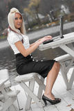 Mobile Business Woman. A beautiful young blonde woman in a mobile business setting with laptop and cell phone royalty free stock photo