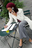 Mobile Career Woman. A successful career woman conducting business outdoors at a table with her cell phone and coffee Royalty Free Stock Photos