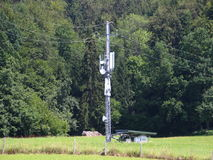 Mobile Cell Phone Distribution Mast with Forest Background. Mobile Cell Phone Ashore Distribution Mast with Forest Background royalty free stock image